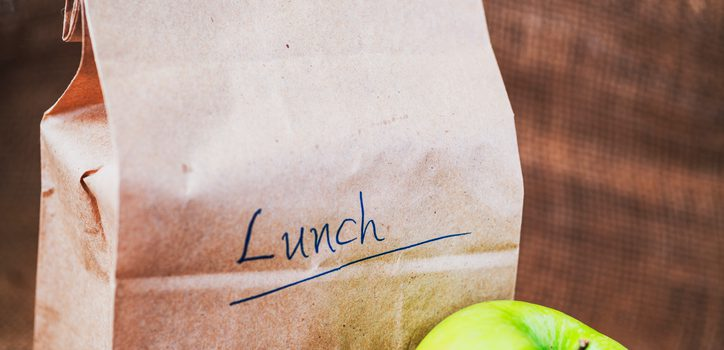 Brown bag lunch and green apple on canvas background and copy space